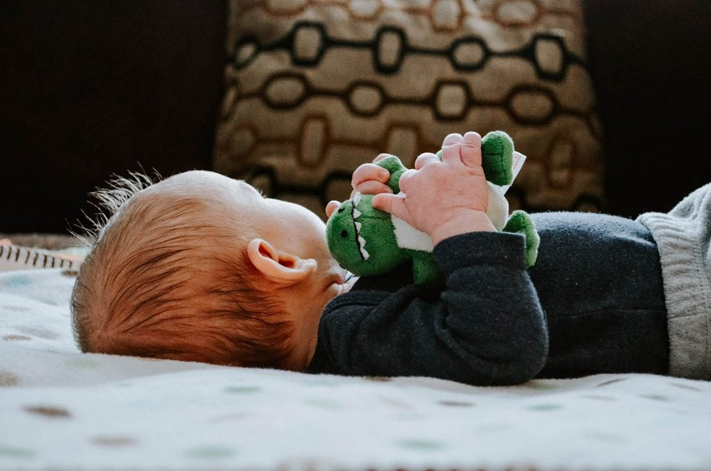 baby lying on a white bed photo