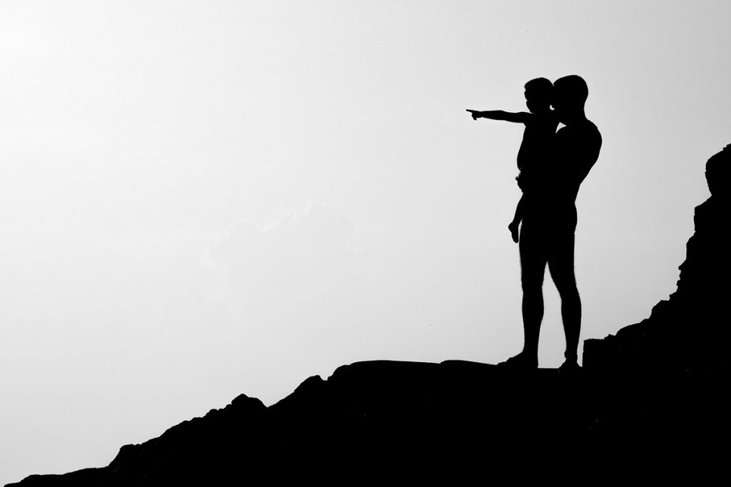 man carrying a baby in silhouette
